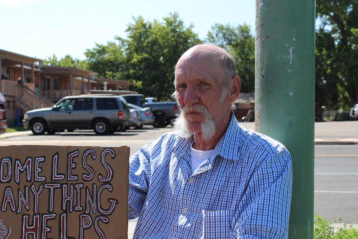 Homeless man holding a sign by a lamppost